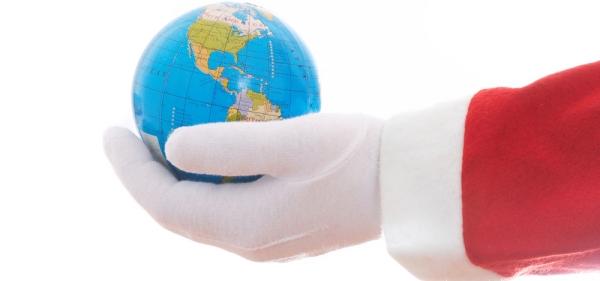 Santa's gloved hand holding a world globe